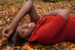 Beautiful Woman Outside in Fall. A portrait of a gorgeous young woman in a bright red sweater Royalty Free Stock Image