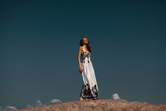 Beautiful woman over the blue sky. Beautiful woman standing on the top of the sand hill Stock Photography