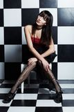 Beautiful woman over chess coloured wall Royalty Free Stock Images
