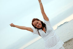 Beautiful woman overjoyed. A beautiful, fit and healthy young woman throws her hands in the air in a fit of joy Royalty Free Stock Images