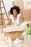 Beautiful woman packing to move house. Beautiful African American woman packing to move house sitting on the hardwood floor in front of a brown cardboard carton Royalty Free Stock Photography