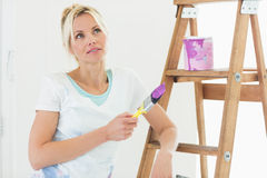 Beautiful woman with paint brush looking away in new house Stock Photography