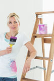 Beautiful woman with paint brush looking away in new house Royalty Free Stock Photo