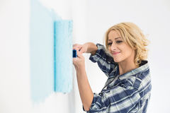 Beautiful woman painting wall with paint roller Royalty Free Stock Photography