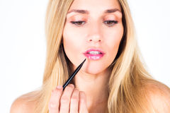 Beautiful woman paints her lips by shine with professional brush. Stock Image