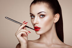 Beautiful woman paints lips with lipstick Royalty Free Stock Images