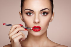 Beautiful woman paints lips with lipstick. Beautiful woman face. Makeup detail. Beauty girl with perfect skin. Red lips and nails manicure Royalty Free Stock Photo