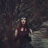 A beautiful woman with pale skin and long red hair in a black dress and in the black crownk. Girl witch with vampire