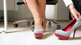 Beautiful young woman in pantyhose taking off sexy high heels shoes under desk in office. Beautiful woman in pantyhose taking off sexy high heels shoes under Royalty Free Stock Photo