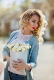 Beautiful woman with paper box of flowers Stock Photo
