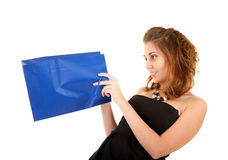 Beautiful woman with papper bag. Beautiful woman in black dress with blue papper bag try to discover what is inside the bag Stock Photo