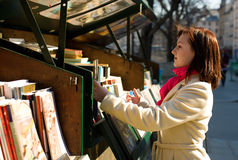 Beautiful woman in Paris. Selecting a book in an outdoor bookseller box royalty free stock image