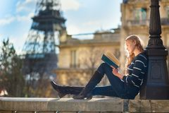 Beautiful woman in Paris, reading a book Stock Photos