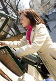 Beautiful woman in Paris selecting a book. In an outdoor bookseller box stock images