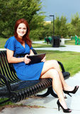 Beautiful Woman on Park Bench. Using tablet Stock Images