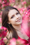 Beautiful woman in a park with pink flowers Royalty Free Stock Image