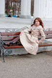 Beautiful woman in a park sits on a bench Royalty Free Stock Photos