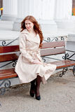 Beautiful woman in a park sits on a bench Royalty Free Stock Images