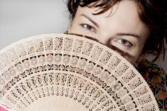Beautiful woman partly hidden behind a fan Stock Images
