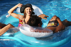Beautiful woman during a party in a swimming pool. Beautiful women drinking coctails during a party in a swimming pool stock images