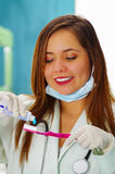 Beautiful woman patient holding a tothpaste in one hand and a tethbrush in her other hand in a dentist`s office. Stock Image