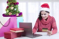 Beautiful woman paying Christmas gifts online Stock Image