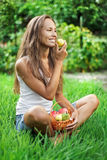 Beautiful woman with pear on the green grass. Beautiful woman with picnic crib eating pear on the green grass. The picture was taken with Carl Zeiss Planar T* 1 royalty free stock photos