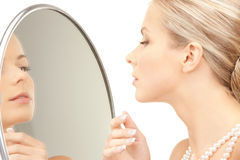 Beautiful woman with pearl beads and mirror Stock Photography