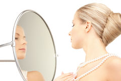 Beautiful woman with pearl beads and mirror Royalty Free Stock Image