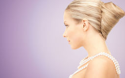 Beautiful woman with pearl necklace over violet Stock Images