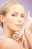 Beautiful woman with pearl necklace over violet Stock Photography
