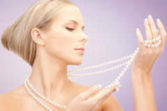 Beautiful woman with pearl necklace over violet Royalty Free Stock Photo