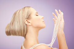 Beautiful woman with pearl necklace over violet Royalty Free Stock Image