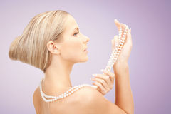 Beautiful woman with pearl necklace over violet Stock Image