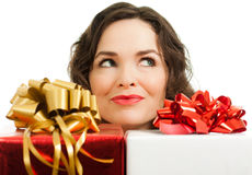 Beautiful woman peeking over presents Stock Photo