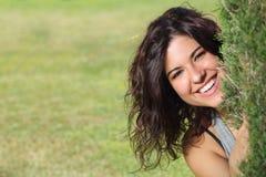 Beautiful woman peeking through a tree and smiling Stock Photo