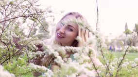 Beautiful woman peeps from behind a flowering bush. Young beautiful woman peeps from behind a flowering bush and laughs stock video footage