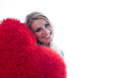 Beautiful woman peering round a red heart Royalty Free Stock Photo