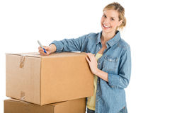 Beautiful Woman With Pen Standing By Stacked Cardboard Boxes Stock Image