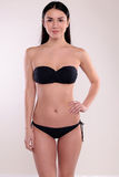 Beautiful woman with perfect body, with dark straight hair wears black bikini Stock Photo