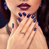 Beautiful woman with perfect make-up and blue manicure wearing jewellery Stock Image