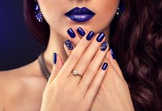 Beautiful woman with perfect make-up and blue manicure wearing jewellery Stock Photo