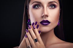 Beautiful woman with perfect make-up and manicure wearing jewellery. On black background stock images