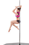 Beautiful woman performing pole dance. Studio shot, on white background, isolated. Cut Royalty Free Stock Image