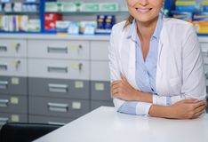 Beautiful woman pharmacist standing at her workplace in pharmacy. Stock Photos