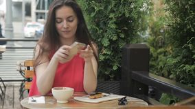 Beautiful woman with phone, eats at summer cafe on street. stock footage
