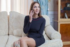 Beautiful woman on the phone in the living room Royalty Free Stock Photos