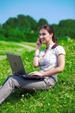 Beautiful  woman with phone and notebook on grass Royalty Free Stock Photo