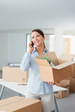 Beautiful woman on the phone with an open box Royalty Free Stock Image