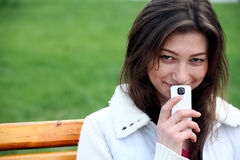 Beautiful woman with phone sits on the bench Royalty Free Stock Photography